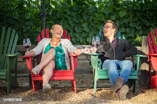 A mixed race couple in their 30s relaxing in Adirondack chairs while drinking wine at a tasting session on a California vineyard.