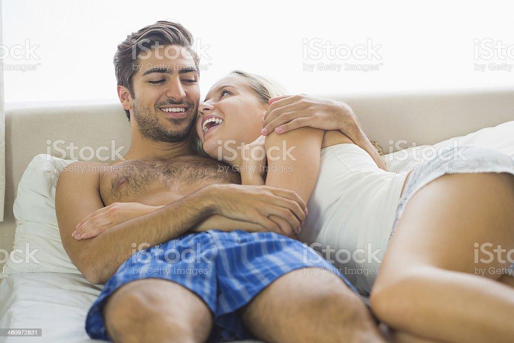Lachen paar liegen auf Bett – Foto