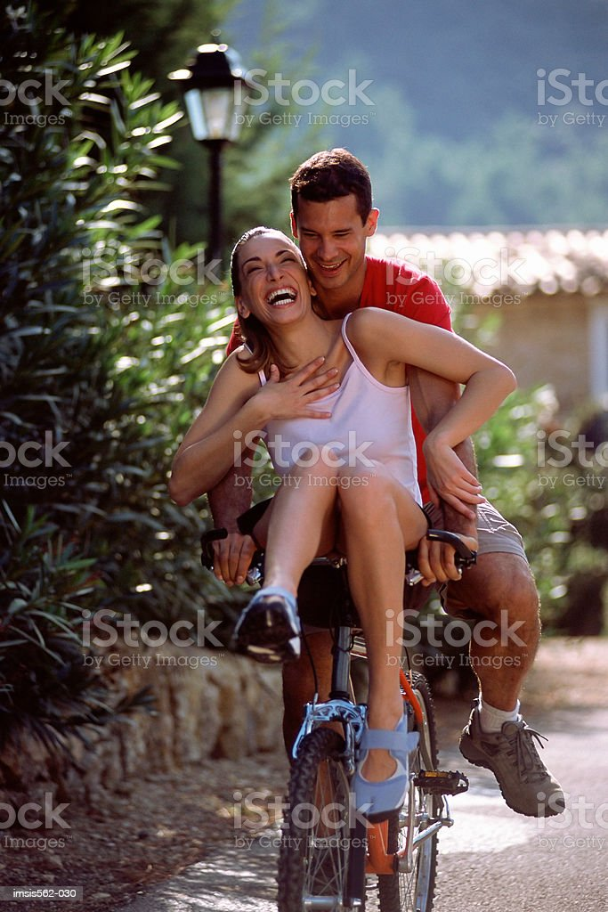 Laughing couple on bicycle royalty-free stock photo