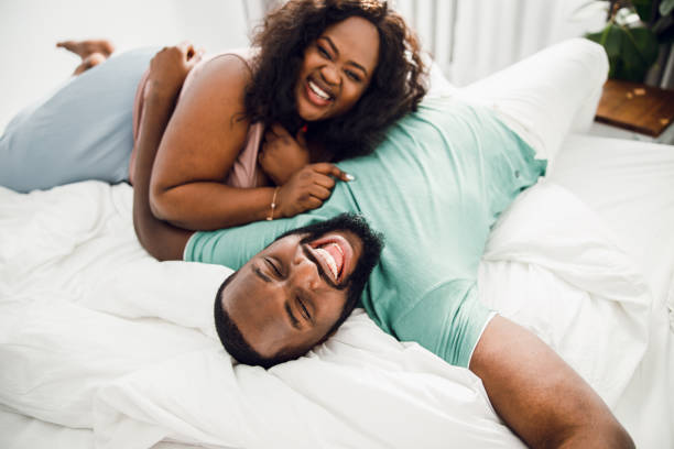 Laughing couple on the white bed stock photo Excited man lying on the bed and laughing with his beloved woman couple in bed stock pictures, royalty-free photos & images