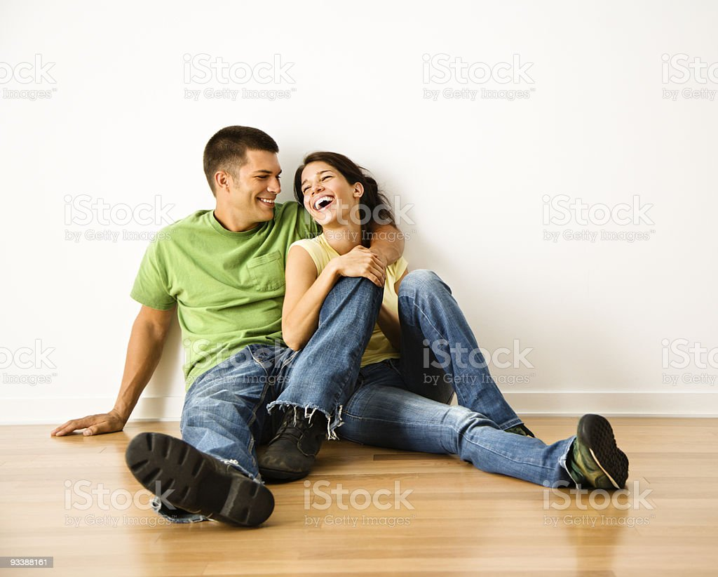 Laughing couple sitting on the floor stock photo