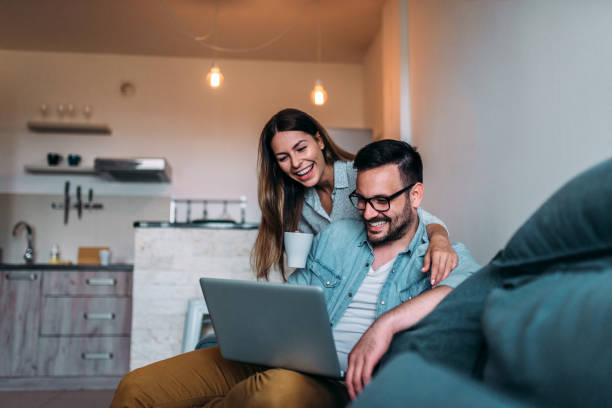 Laughing couple watching something funny on laptop. stock photo