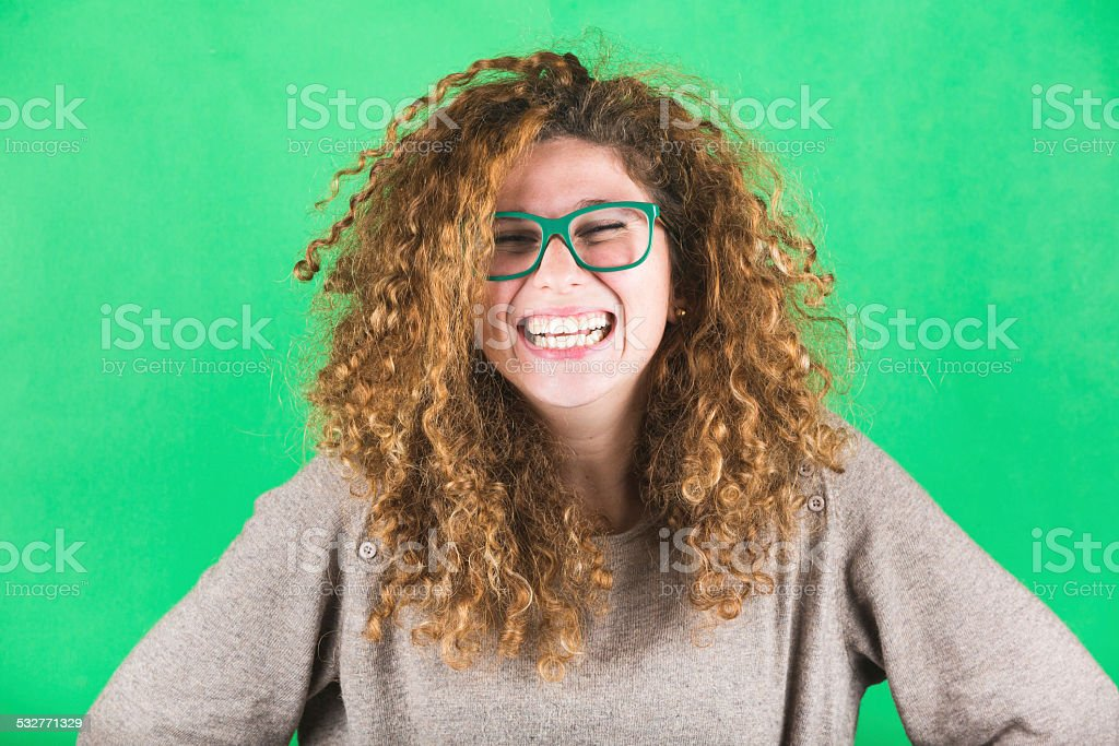 Laughing Curly Woman on Green Background stock photo