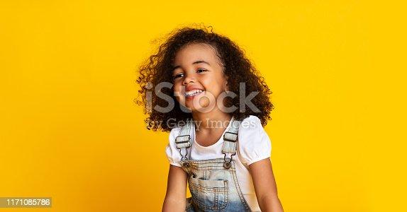 Laughing cute afro girl portrait, kid hearing joke over yellow studio background