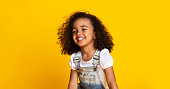 Laughing cute afro girl portrait, kid hearing joke over yellow studio background