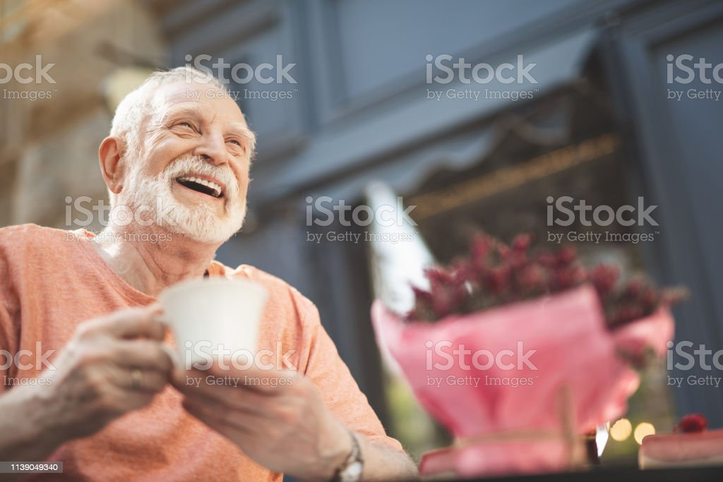 Laughing elderly man drinking tea outdoors Low angle waist up portrait of delighted mature male sitting at table outside. He is holding cup of hot drink and looking with pleasure and content. Copy space in right side Adult Stock Photo