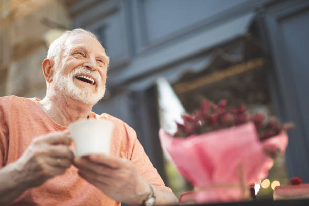 Laughing elderly man drinking tea outdoors Low angle waist up portrait of delighted mature male sitting at table outside. He is holding cup of hot drink and looking with pleasure and content. Copy space in right side one senior man only stock pictures, royalty-free photos & images
