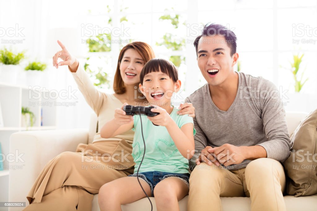 Laughing Family Playing Video Games In Living Room Stock