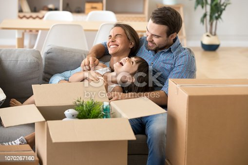 istock Laughing family spend time having fun at new home 1070267160