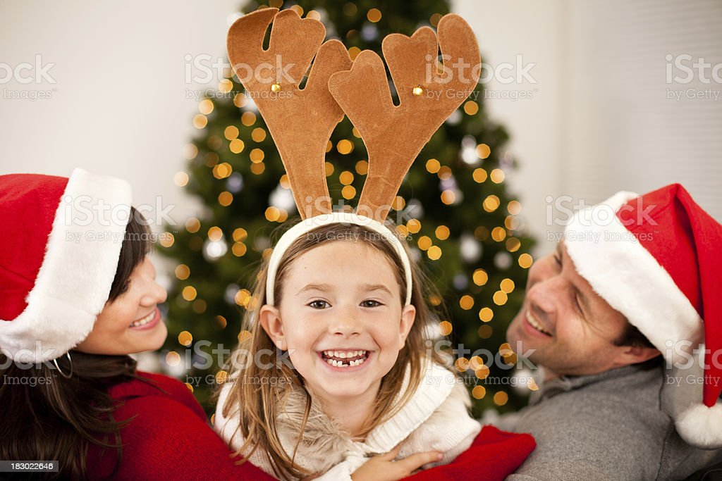 9fa743e33 Laughing Family Wearing Antlers And Santa Hats With Christmas Tree ...