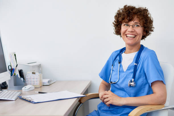 Laughing Female Doctor at Desk in Office stock photo