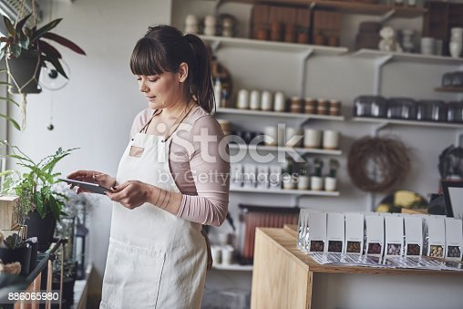 Young female florist checking her online orders with a digital tablet while standing in her flower shop