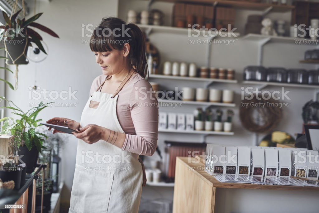 Laughing florist arranging a floral display in her shop stock photo