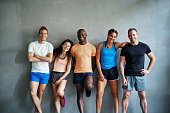 istock Laughing friends in sportswear standing together in a gym 932448170