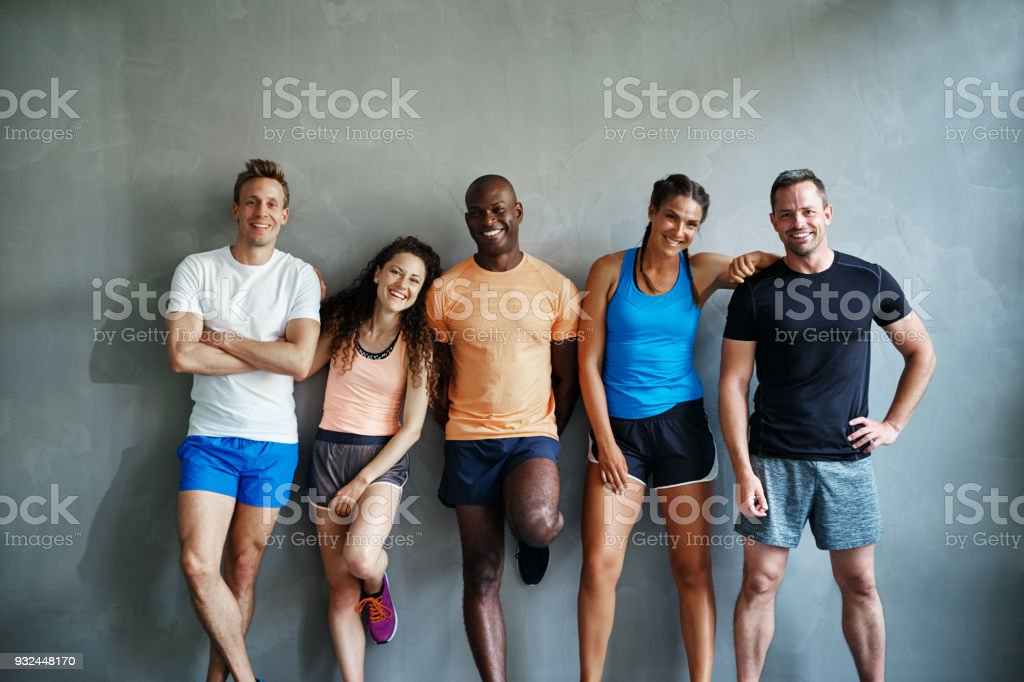 Laughing friends in sportswear standing together in a gym stock photo
