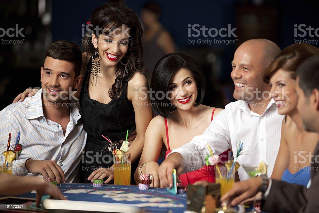 Ridendo gli amici giocando a carte in un casinò - foto stock