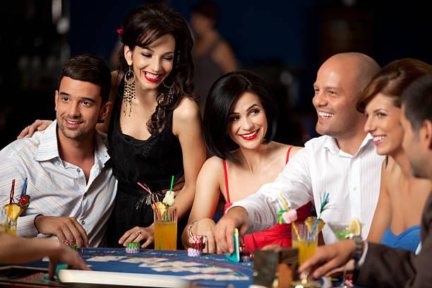 laughing friends playing cards in casino - black jack bildbanksfoton och bilder