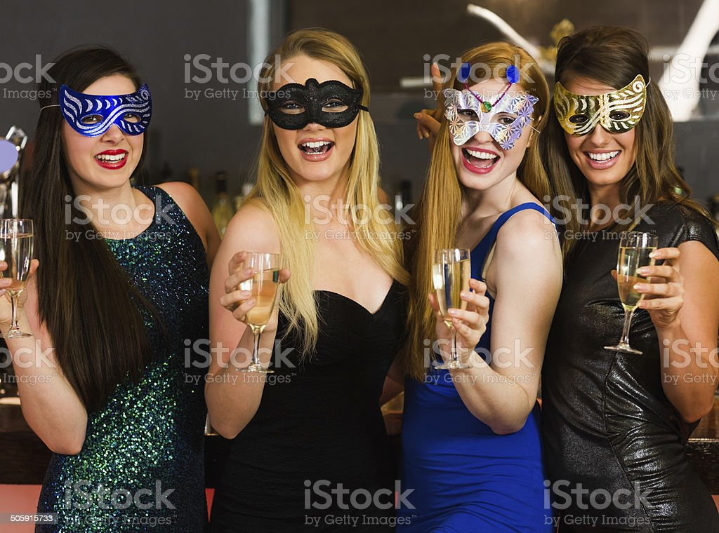Laughing friends wearing masks holding champagne glasses stock photo