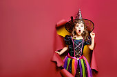 istock Laughing funny child girl in a witch costume in halloween 1166666423