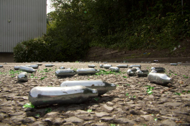 Laughing Gas Canisters Discarded Nitrous gas canisters in a car park. Nitrous oxide is a colourless gas that when inhaled can make people feel euphoric and relaxed. nitrous oxide stock pictures, royalty-free photos & images