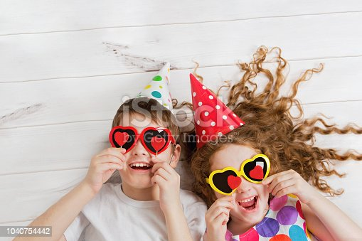 865399512istockphoto Laughing girl and boy with sunglasses, hold candles heart form. 1040754442