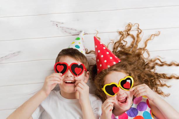 Lachen Mädchen und jungen mit Sonnenbrille, halten Sie Kerzen Herzform. – Foto