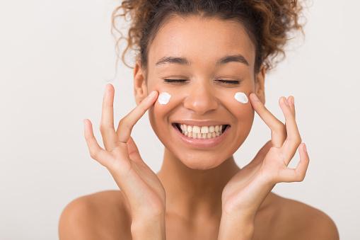 istock Laughing girl applying moisturizing cream on her face 1125908113