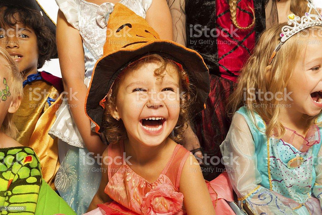 Niña sonriente en traje de Halloween con amigos - foto de stock