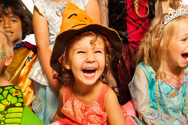 Laughing girl in Halloween costume with friends Little laughing girl wearing dress and Halloween hat surrounded by friends kids, close-up studio portrait carnival children stock pictures, royalty-free photos & images