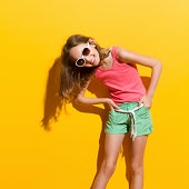 Laughing girl in sunlight. Three quarter length studio shot on yellow background.