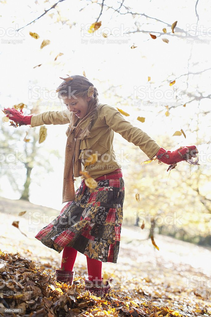 Laughing girl playing in pile of autumn leaves royalty free stockfoto