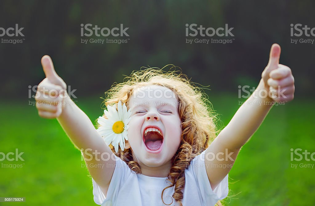 Laughing girl with daisy in her hairs, showing thumbs up.
