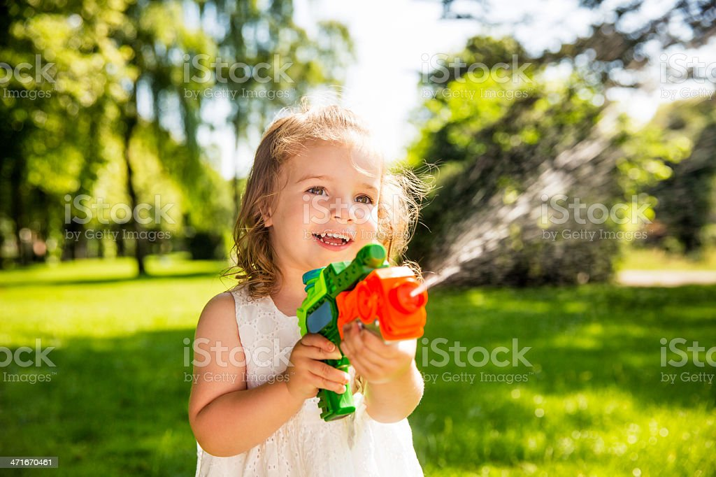 Laughing Girl splashing water with a squirt gun stock photo