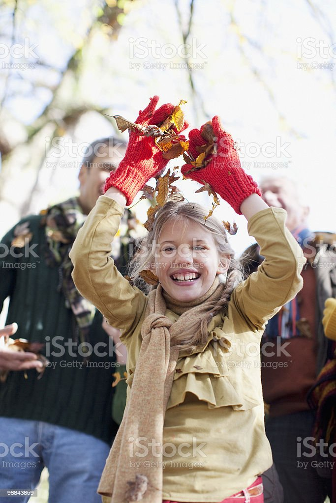 Laughing girl throwing autumn leaves royalty-free stock photo