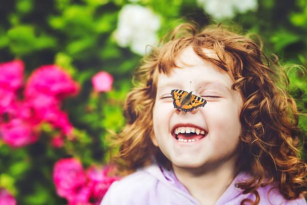 Lachen Mädchen mit einem Schmetterling auf seine Nase – Foto