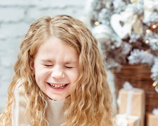 Lachen Mädchen sitzend mit geschlossenen Augen unter dem Weihnachts-Baum – Foto