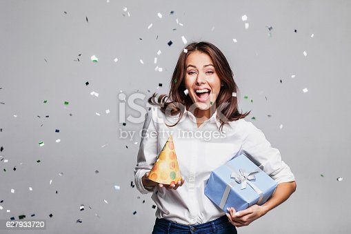 istock Laughing girl with falling confetti at party 627933720