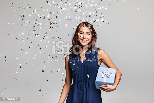 istock Laughing girl with falling confetti at party 627933752