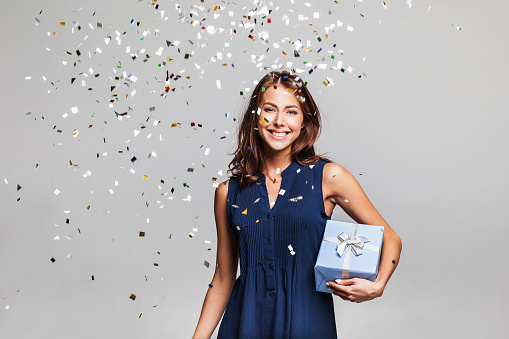 627933752 istock photo Laughing girl with falling confetti at party 627933752