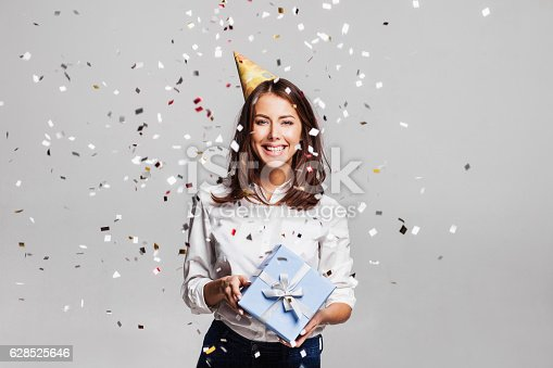 istock Laughing girl with falling confetti at party 628525646