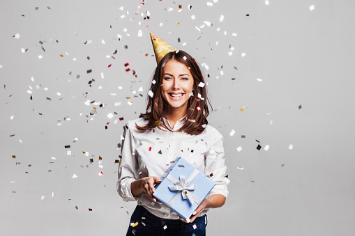 627933752 istock photo Laughing girl with falling confetti at party 628525646