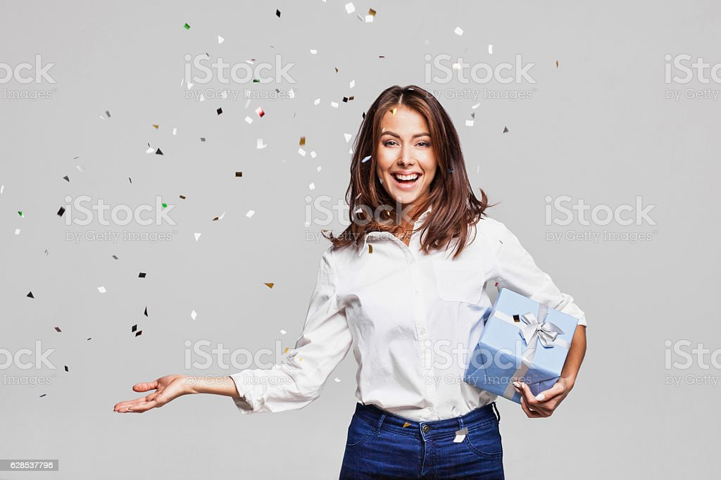 Laughing girl with falling confetti at party Beautiful woman with confetti and gift box at party on gray background Adult Stock Photo
