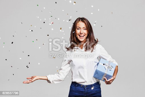 istock Laughing girl with falling confetti at party 628537796