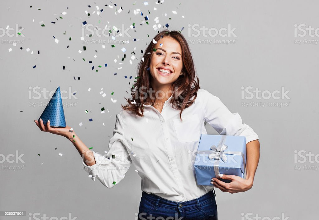 Laughing girl with falling confetti at party stock photo
