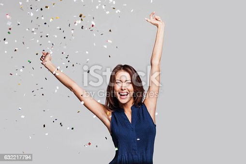 istock Laughing girl with falling confetti at party 632217794