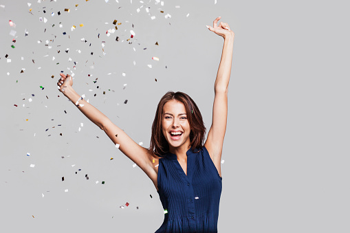 627933752 istock photo Laughing girl with falling confetti at party 632217794