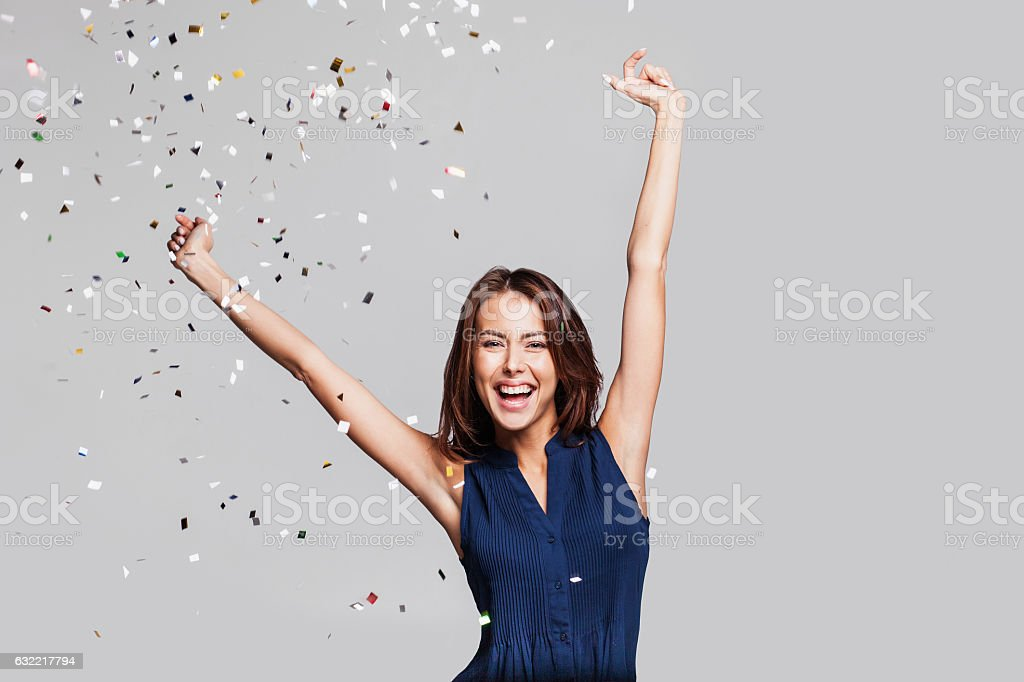 Laughing girl with falling confetti at party - foto de stock