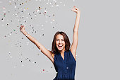 Laughing girl with falling confetti at party