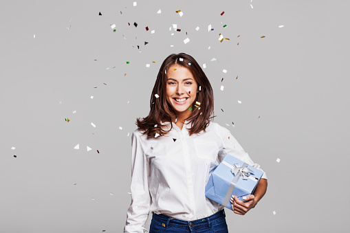 627933752 istock photo Laughing girl with falling confetti at party 638797782