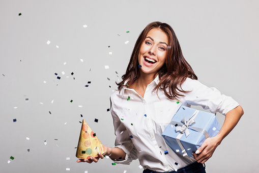 627933752 istock photo Laughing girl with falling confetti at party 638797800